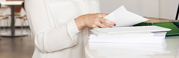 Lady_standing_at_a_table_with_a_stack_of_office_paper.jpg